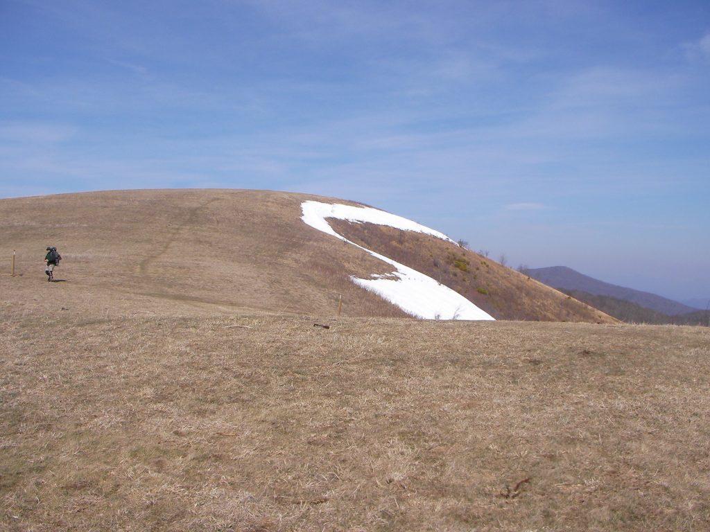 A hiker follows the Appalachian Trail across Max Patch Bald