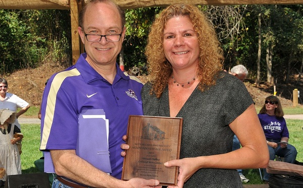 WCU Chancellor David O. Belcher (left) presents a Mountain Heritage Award to the Stecoah Valley Cultural Arts Center, which is represented by its director, Beth Fields (right.)