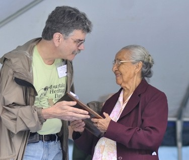 Cherokee pottery-maker Amanda Swimmer was honored at WCU's Mountain Heritage Day festival on Saturday as the individual recipient of the university's Mountain Heritage Award. Swimmer has demonstrated pottery making at Oconaluftee Indian Village in Cherokee for more than 40 years. She is shown accepting the award from Scott Philyaw, chairman of the Mountain Heritage Day organizing committee.