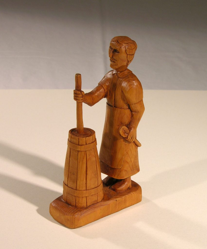 A wood carving of a woman churning butter.  Courtesy of the Mountain Heritage Center.